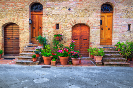 Traditional Tuscany architectural view. Fantastic entrance and paved street decorated with colorful flowers in Pienza, Tuscany, Italy, Europe Stockfoto - 114809907