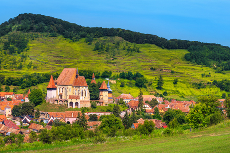 Beautiful travel destination, agricultural area and famous saxon fortified church with Transylvanian village in background, Biertan, Transylvania, Romania, Europe 스톡 콘텐츠