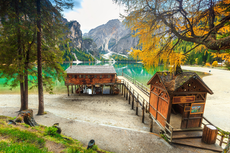 Beautiful autumn alpine landscape, spectacular old wooden dock house with pier on the lake and typical wooden boats, Braies lake, Dolomites, Italy, Europe
