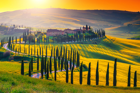 Berühmter beliebter Ort für Reisen und Fotografie. Majestätischer bunter Sonnenuntergang und landwirtschaftliches Feld mit typischen toskanischen Steinhäusern auf dem Hügel, in der Nähe der touristischen Stadt Siena, Italien, Europa