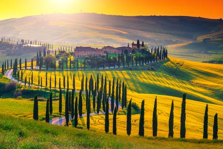 Célèbre lieu de voyage et de photographie populaire. Coucher de soleil coloré majestueux et champ agricole avec des maisons en pierre typiques de la Toscane sur la colline, près de la ville touristique de Sienne, Italie, Europe