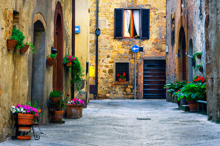Amazing travel destination in Tuscany, rustic traditional decorated street with colorful flowers and rural stone houses, Pienza, Tuscany, Italy, Europe