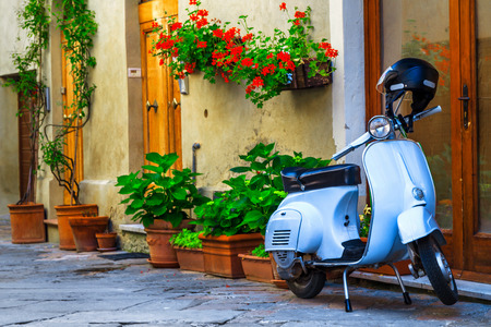Gorgeous cute decorated street with flowers and rustic entrance, old fashioned scooter standing in typical Italian street, Pienza, Tuscany, Europe