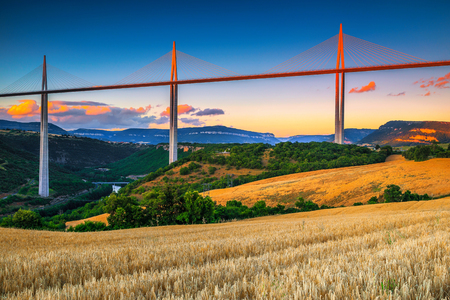 Amazing architectural and touristic location. Admirable viaduct of Millau and grain fields at sunset, Aveyron region, France, Europe