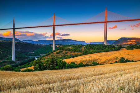 Emplacement architectural et touristique incroyable. Admirable viaduc de Millau et champs de céréales au coucher du soleil, région de l'Aveyron, France, Europe