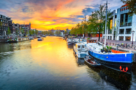 Admirable travel and touristic destination, gorgeous cityscape with traditional dutch houses. Water canal with houseboats at sunset, Amsterdam, Netherlands, Europe Stockfoto