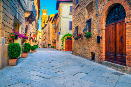 Spectacular traditional Tuscany street view. Admirable medieval stone houses and paved street with flowery entrances, Pienza, Tuscany, Italy, Europe