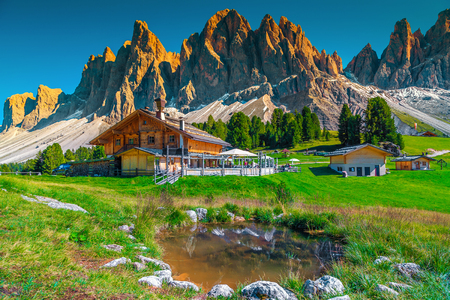 Beautiful spring alpine landscape, mountain chalets and small lake with high snowy mountains in background at sunset, Geisler - Odle mountain group, Alto Adige, Dolomites, Italy, Europe