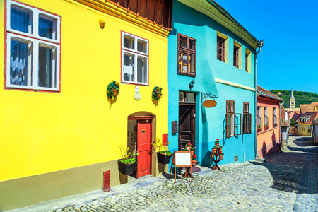 Stunning saxon street with colorful buildings. Wonderful paved street with souvenir shop and restaurant in Sighisoara, Transylvania, Romania, Europe Foto de archivo