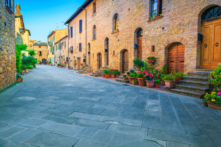 Fantastic travel location in Tuscany, charming traditional decorated street with colorful flowers and retro brick houses, Pienza, Tuscany, Italy, Europe Stockfoto - 120945083