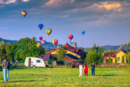 Stunning colorful hot air balloons at sunrise. Touristic village and camping place with tourists looking at view the colorful hot air balloons, Sovata, Transylvania, Romania, Europe