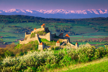 Fantastic tourist attraction and travel location. Well-known Rupea fortress and snowy mountains in background at sunrise, Brasov, Transylvania, Romania, Europe