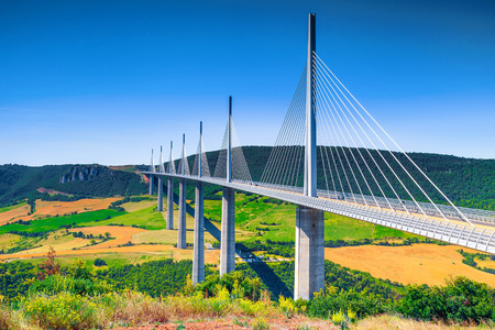 The best known locations of world,  wonderful viaduct of Millau with agriculture fields, Aveyron region, France, Europe Фото со стока