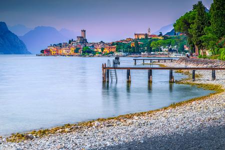 Wonderful summer vacation and relaxation resort, Malcesine touristic place, breathtaking gravel beach at sunset, Garda lake, Veneto region, Italy, Europe