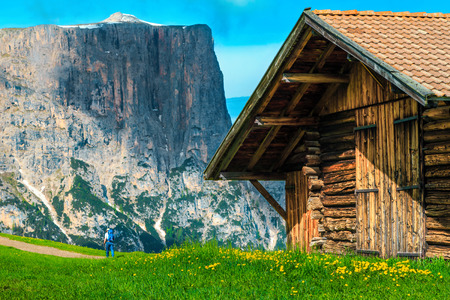 Beautiful summer holiday location, traditional alpine wooden house with backpacker tourist and high mountains in background, Alpe di Siusi - Seiser Alm resort, Dolomites, Italy, Europe Stok Fotoğraf
