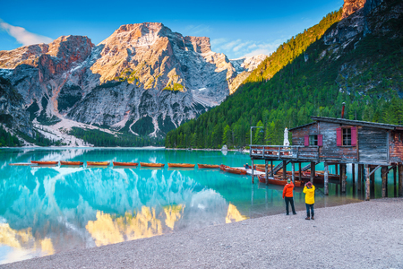Famous popular alpine touristic, recreation, hiking and photography place. Tourists and photographers on the shore. Lake Braies with boathouse and wooden boats, Dolomites, Italy