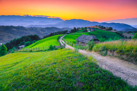 Fantastic travel destination, majestic summer rural landscape, green fields and wooden houses with gardens at sunset, Bran, Transylvania, Romania, Europe