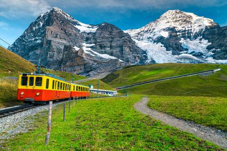 Wunderschönes Sommerreiseerlebnis, beliebter elektrischer roter Touristenzug mit hohen schneebedeckten Schweizer Bergen im Hintergrund, in der Nähe des Bahnhofs Kleine Scheidegg, Berner Oberland, Schweiz, Europa