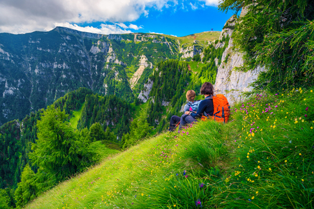 Sporty woman's hiking team with colorful backpacks relaxing and enjoying the view on narrow trekking trail, Bucegi mountains, Carpathians, Transylvania, Romania, Europe Banque d'images