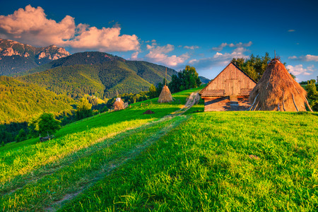 Beautiful summer alpine countryside landscape, hay bales with wooden hut and high mountains in background at sunset, Bran, Transylvania, Romania, Europe