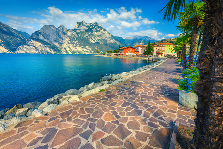 Fantastic promenade decorated with colorful mediterranean flowers. Amazing landscape with high mountains and lake Garda, Torbole, Italy, Europe