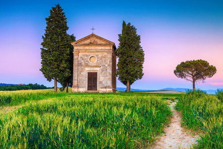 Well known photography and touristic place in Tuscany, stunning Vitaleta chapel in summer grain field at colorful sunset, Pienza, Tuscany, Italy, Europe Stockfoto