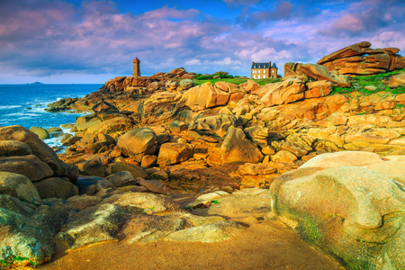 Picturesque sunset with lighthouse of Ploumanach Mean Ruz in Perros-Guirec. Pink Granite Coast and stunning tidal place with granite cliffs, Brittany, France, Europe