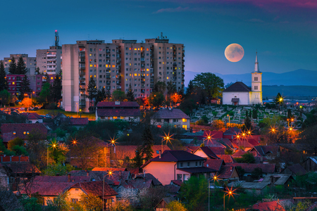 Picturesque evening scene. City landscape at night with full moon, Sfantu Gheorghe, Transylvania, Romania, Europe