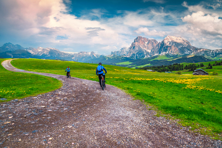 Active happy couple cycling outdoors. Healthy lifestyle with mountain bike, couple cycling on the mountain road in the Alps, Dolomites, Italy, Europe
