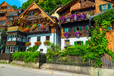 Popular touristic village street view, flowery wooden houses with ornamental gardens and entrances in famous Hallstatt, Salzkammergut region, Austria, Europe
