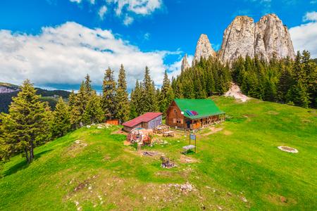 Paysage alpin d'été pittoresque, chalet en bois de montagne et hautes falaises, Piatra Singuratica, (roche solitaire), montagnes Hasmasul Mare en Transylvanie, Roumanie, Europe