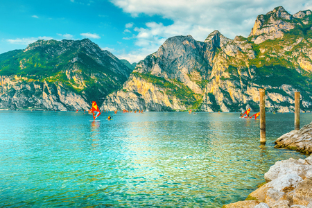 Popular summer holiday and leisure location, surfers exercising in lake near Riva del Garda resort, lake Garda, Italy, Europe