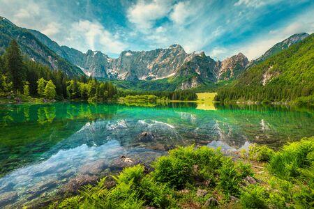 Stunning mountain landscape and hiking place. Spectacular superior Fusine lake and Mangart peak in background, Julian Alps, Tarvisio, Udine region, Friuli Venezia Giulia, Italy, Europe Imagens - 129683931