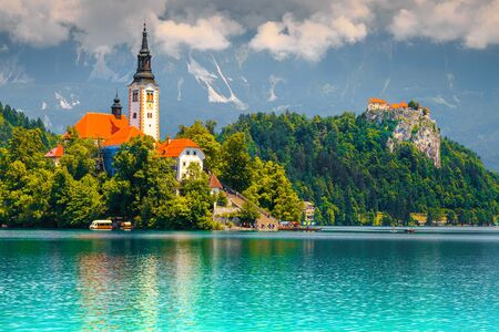 Beautiful travel and excursion place. Popular and stunning lake Bled with picturesque Pilgrimage church on small green island, Bled, Slovenia, Europe Imagens - 129683942