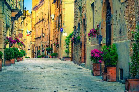 Malowniczy tradycyjny widok na ulicę Toskanii. Piękne średniowieczne kamienne domy i brukowana ulica z kwiecistymi wejściami, Pienza, Toskania, Włochy, Europa