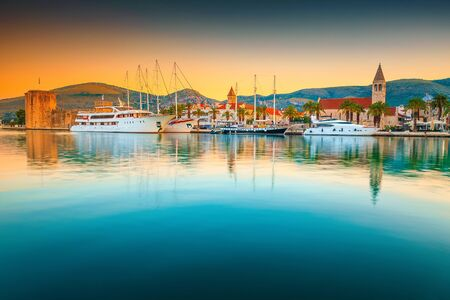 Famous travel and vacation destination. Amazing colorful sunrise, harbor with boats and luxury yachts. Medieval and historic old town, Trogir, Croatia, Europe Stock Photo