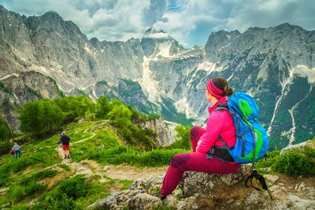 Active hiking woman with colorful backpack. Hiker woman relaxing and enjoying the view with Jalovec mountain peak, from the Slemenova Spica hiking place, Julian Alps, Slovenia, Europe Imagens - 129683954