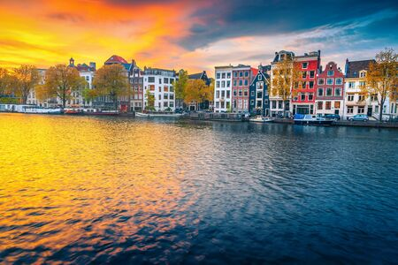 Popular travel and touristic destination. Picturesque autumn cityscape with traditional dutch houses. Water canal with houseboats at sunset, Amsterdam, Netherlands, Europe 스톡 콘텐츠