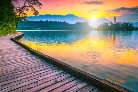 Majestic morning view with small island, church and castle from the wooden promenade. Famous travel and touristic location, lake Bled with Karavanke mountains in background at sunrise, Slovenia, Europe