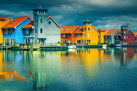 Picturesque touristic and university Dutch city. Spectacular Reitdiephaven street with traditional colorful modern wooden houses on water, Groningen, Netherlands, Europe 스톡 콘텐츠