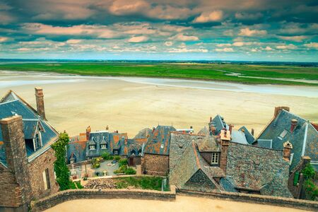Famous travel and excursion place. Old stone houses with gardens and tidal island. Breathtaking view from the village of Mont Saint Michel, Normandy, France, Europe