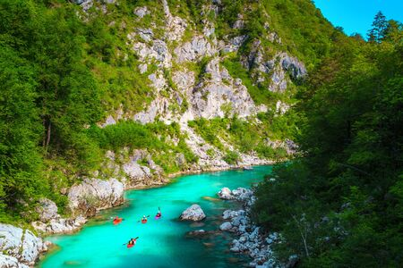 Popular rafting and kayaking locations. Active kayakers paddling on the emerald color Soca river, near Kobarid, Triglav National Park, Slovenia, Europe