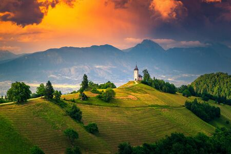 Mountain landscape with church on the hill. Beautiful colorful sunset landscape and spectacular Saint Primoz church with high mountains in background, Jamnik village, Slovenia, Europe