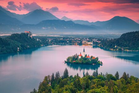 Magical evening view with small island, church and castle from the hill. Popular travel and touristic location, lake Bled with small island and Karavanke mountains in background at sunset, Slovenia, Europe Imagens