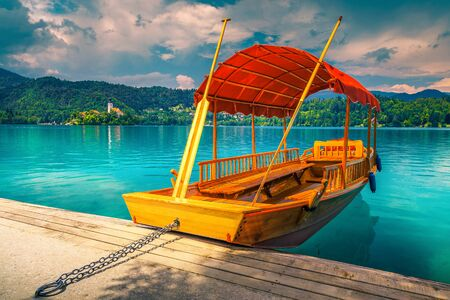 Fantastic traditional wooden Pletna boat moored at the pier. Cute Pletna boat on the turquoise lake Bled and Pilgrimage church with small island in background, Slovenia, Europe