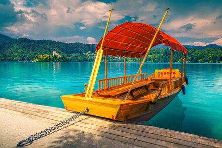 Fantastyczna tradycyjna drewniana łódź Pletna zacumowana przy molo. Ładna łódź Pletna na turkusowym jeziorze Bled i kościół pielgrzymkowy z małą wyspą w tle, Słowenia, Europa Zdjęcie Seryjne