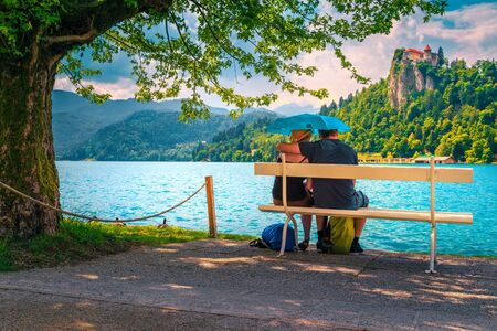 Adult romantic couple sitting and embracing on the bench in the rain with umbrella. Carefree couple in love enjoying the lake and castle. Happy love couple hugging on the bench, Bled, Slovenia Imagens