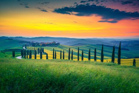 Beautiful colorful sunset in Tuscany. Spectacular agrotourism and typical curved road with cypress. Crete Senesi rural landscape with grain plantation in Tuscany, Italy, Europe