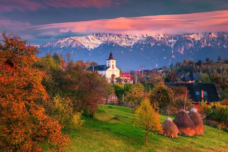 Picturesque autumn alpine landscape, amazing alpine village with gardens, haystacks and high snowy mountains in background near Bran, Magura, Transylvania, Romania, Europe