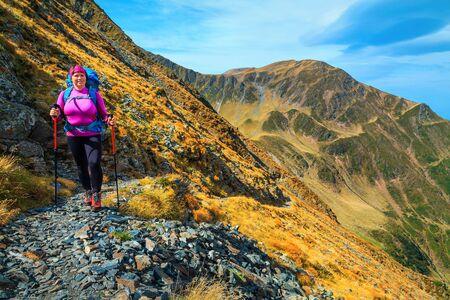Glückliche aktive sportliche Wandererin mit Rucksack auf alpinen Wanderwegen, Fagaras-Gebirge, Wander- und Reisekonzept, Karpaten, Rumänien, Europa